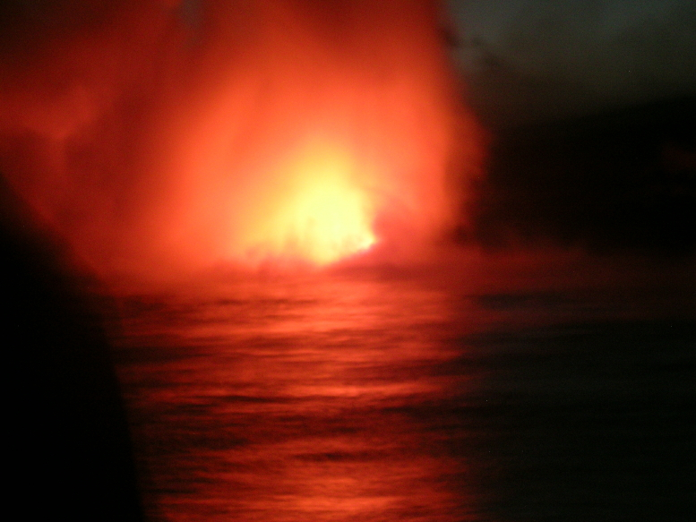 The base of Kilauea, where the lava flows into the sea, creating the foundation for new land, new life.  As fire and lava meet cool water, light flashes to signify the birth of new life at the bottom of the sea.